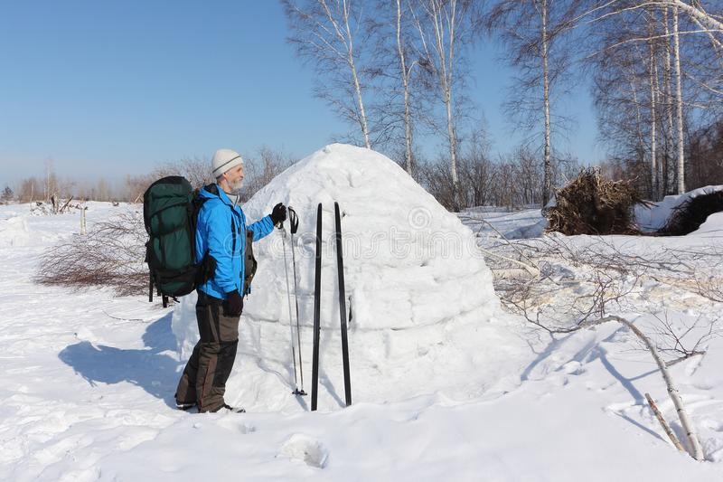 Équipez le skieur se tenant prêt un igloo sur une clairière photos libres de droits