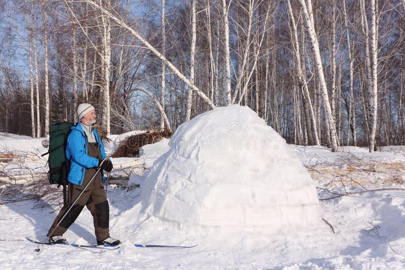 Équipez le skieur se tenant prêt un igloo sur une clairière photo stock