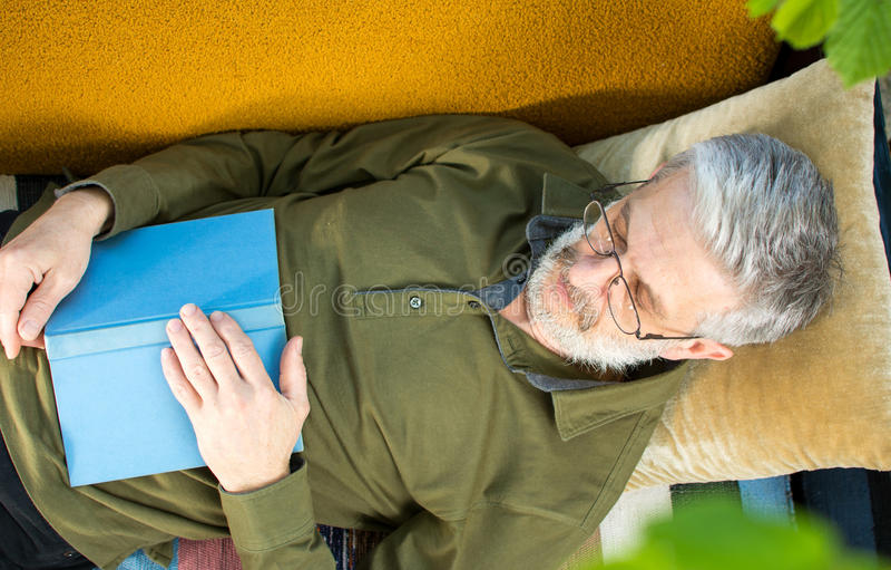 Équipez le sommeil avec un livre sur un canapé-lit photos libres de droits