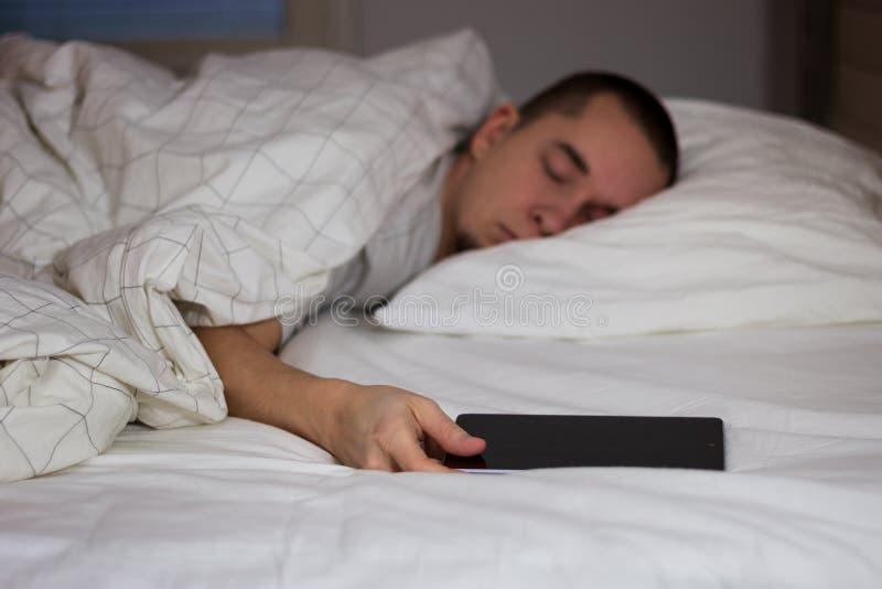 Équipez le sommeil dans le lit et tenir une tablette photo stock