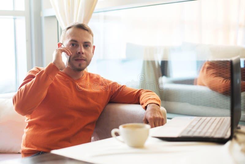 Équipez le travail avec le carnet, parlant au téléphone, en café photos libres de droits