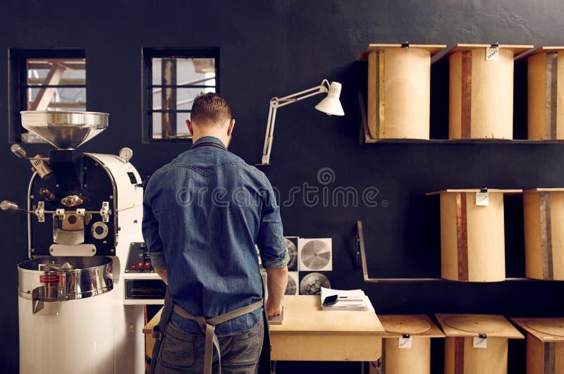 Équipez le travail dans son roastery moderne de café avec le stockage ordonné photographie stock libre de droits