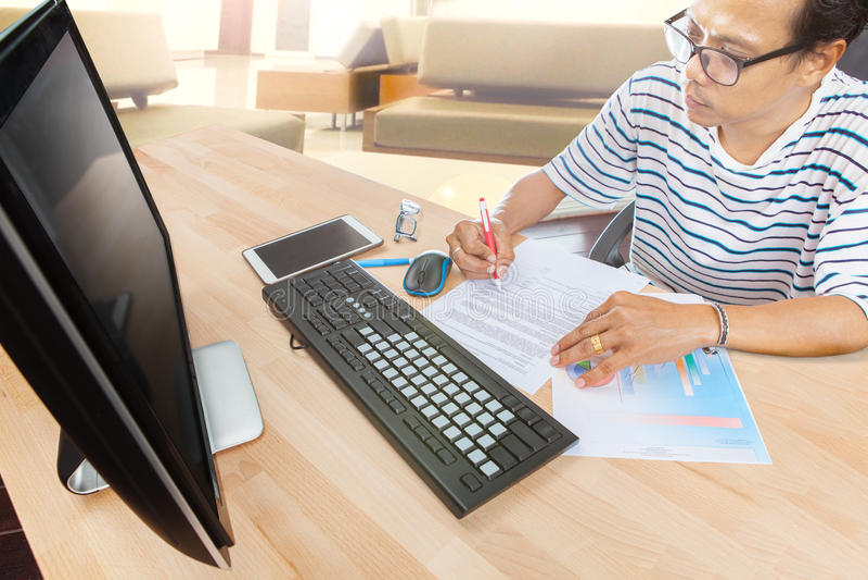 Équipez le travail par ordinateur sur le salon de table à la maison photo stock