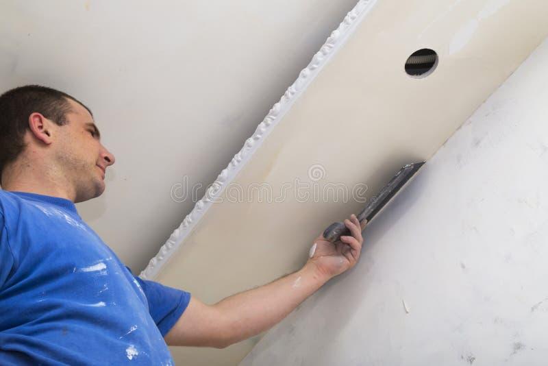 Équipez le travailleur appliquant la couche de mastic avec la truelle photo stock