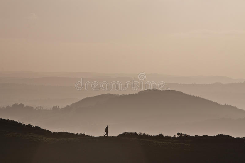 Équipez le trekking sur une montagne avec un fond rose flou photos stock