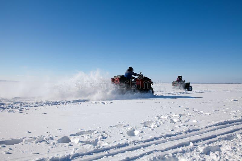Équipez le vélo de quadruple d'équitation sur le champ neigeux d'hiver photos stock