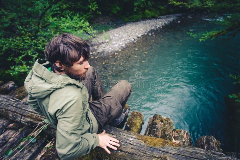 Équipez le voyageur détendant sur le pont en bois au-dessus de la rivière photos stock