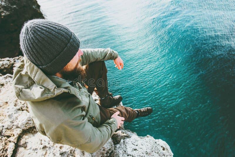 Équipez le voyageur s'asseyant sur la seule pensée de falaise au-dessus de la mer profonde image stock