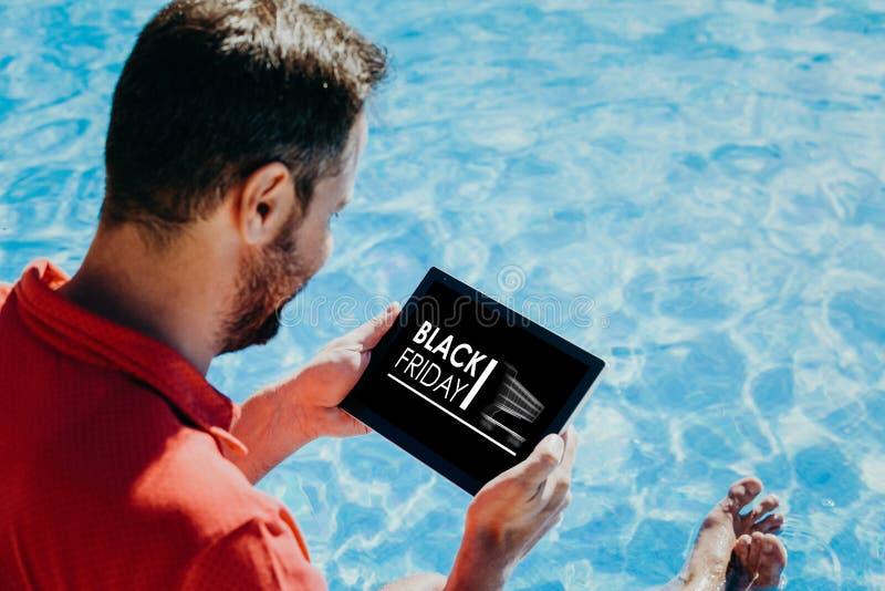 Équipez les achats par des offres spéciales de Black Friday d'Internet avec un comprimé électronique image stock