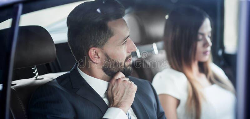 Équipez les affaires avec un exécutif de collègue voyageant en taxi image libre de droits