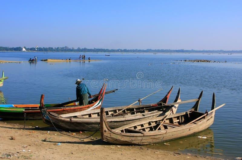 Équipez les bateaux en bois proches debout au lac, Amarapura, Myanmar photos stock