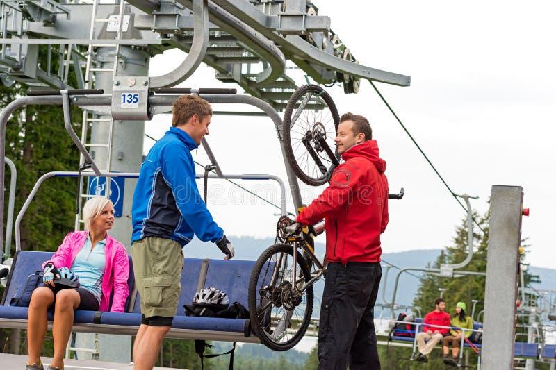 Couples de aide d'homme tenant l'ascenseur de chaise de bicyclette photos libres de droits