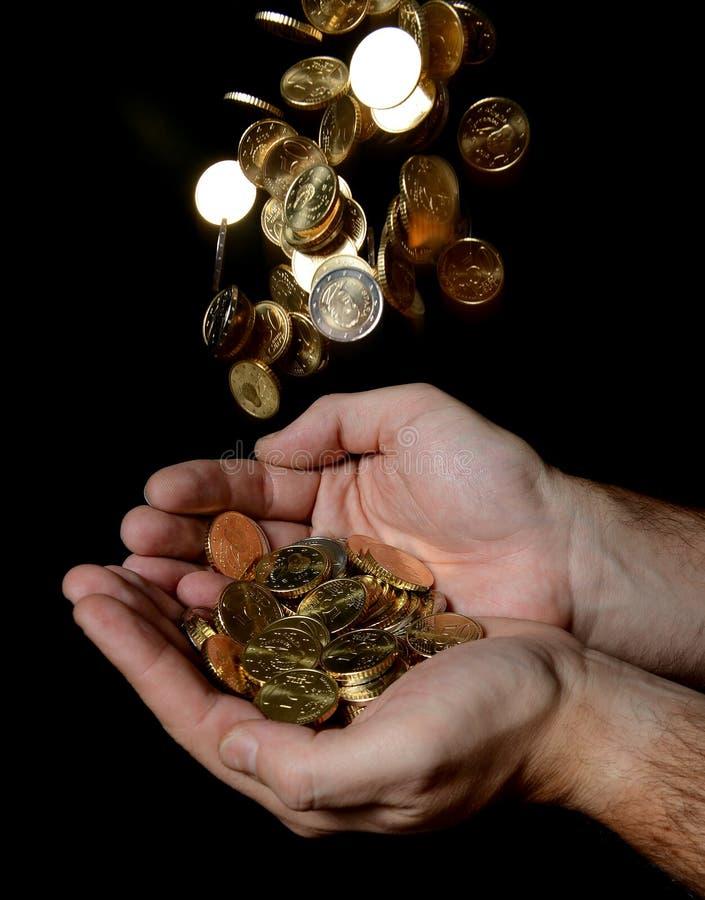 Équipez les mains complètement de l'argent recevant une pluie des pièces de monnaie image stock
