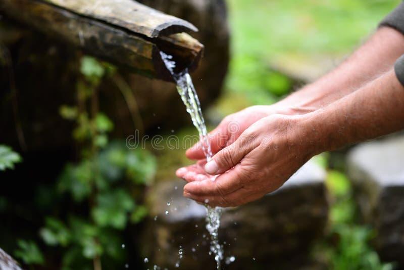 Équipez les mains de lavage dans l'eau fraîche, froide, potable photos libres de droits