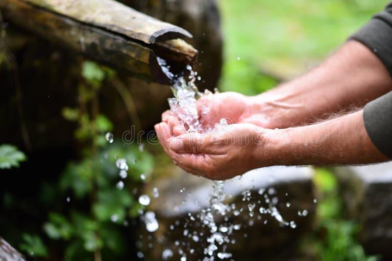Équipez les mains de lavage dans l'eau fraîche, froide, potable photos stock