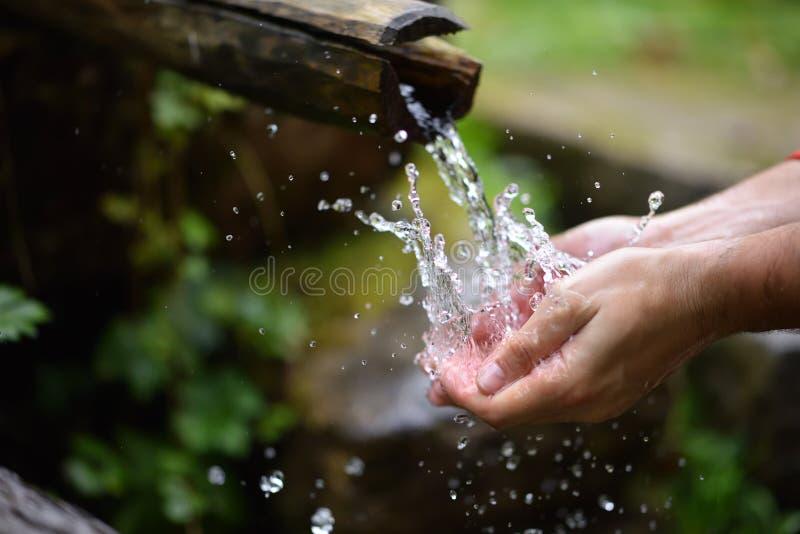 Équipez les mains de lavage dans l'eau fraîche, froide, potable photo stock