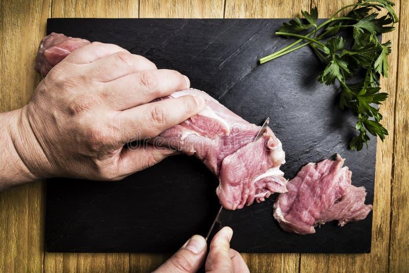 Équipez les mains du ` s dédoublant un filet de porc avec un couteau à côté de quelques branches de persil sur une gauffreuse noi image libre de droits
