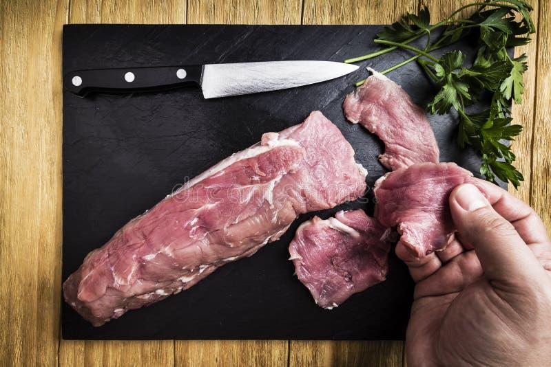 Équipez les mains du ` s dédoublant un filet de porc avec un couteau à côté de quelques branches de persil sur une gauffreuse noi images stock
