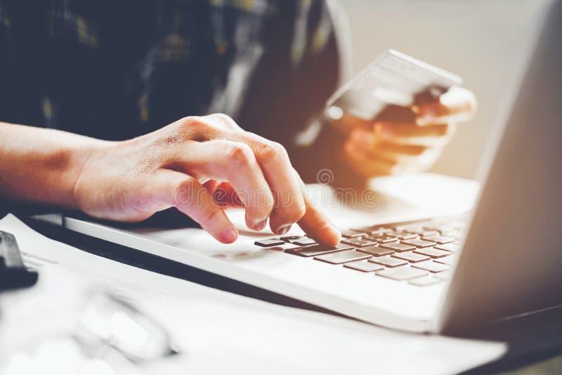 Équipez les mains du ` s dactylographiant le clavier d'ordinateur portable et tenant l'onlin de carte de crédit image libre de droits
