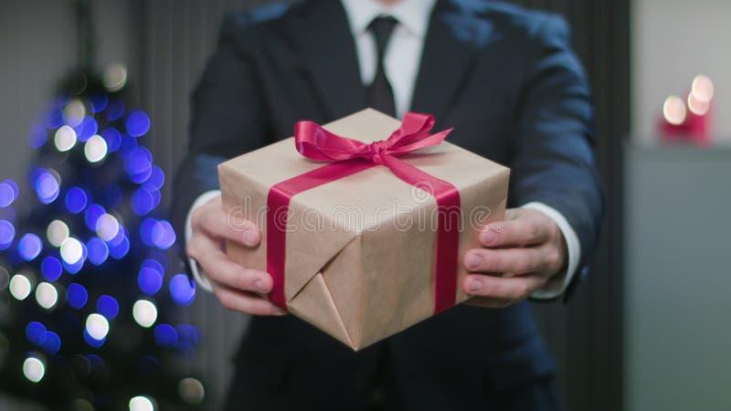 Équipez les mains du ` s tenant un cadeau de Noël images libres de droits