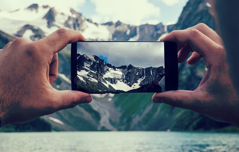 équipez les mains tenant le téléphone portable en mer et des montagnes image libre de droits