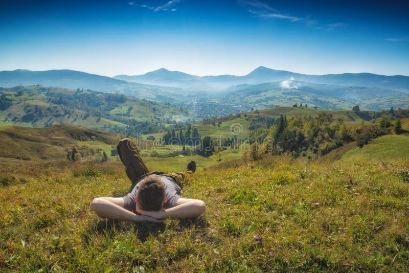 Équipez les mensonges sur une colline dans une herbe et appréciez la vallée image libre de droits