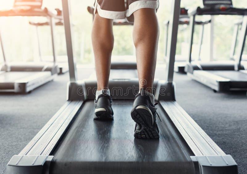 Équipez les pieds du ` s sur le tapis roulant dans le centre de fitness, mode de vie sain image stock