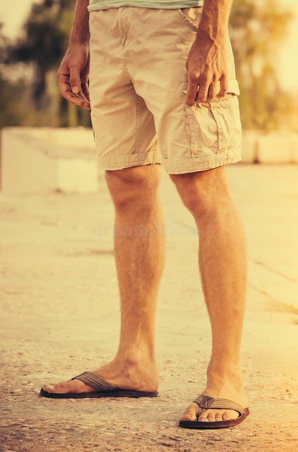 Équipez les pieds portant des caleçons et les bascules électroniques tenant l'été extérieur images libres de droits