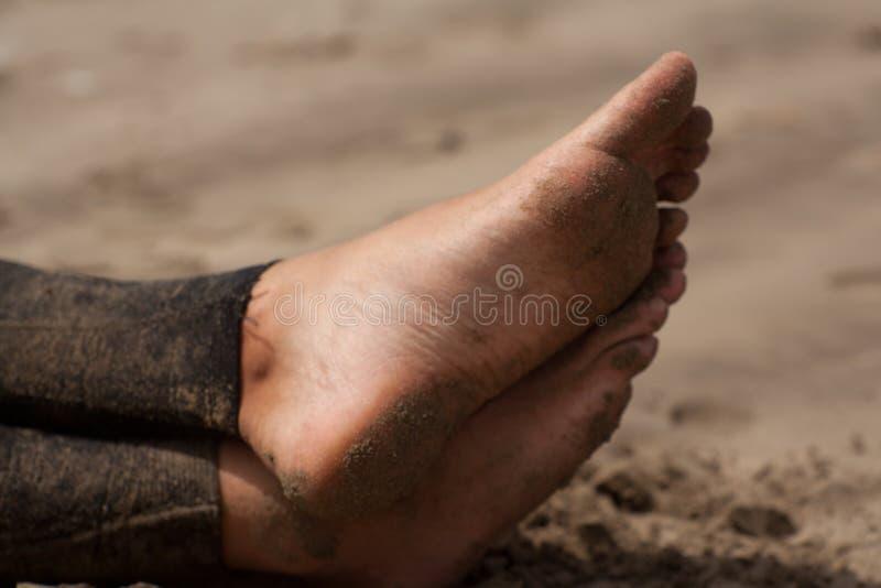Équipez les pieds, surfer avec le wetsuite se reposant sur la plage attendant les vagues image stock