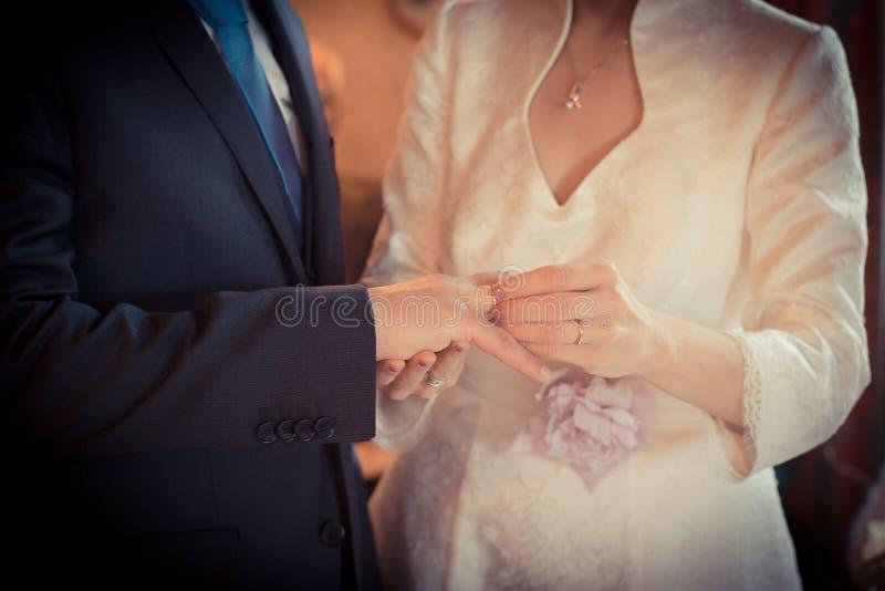 Équipez mettre l'anneau de mariage à son doigt du ` s de jeune mariée, fin, arrangement idyllique photos stock