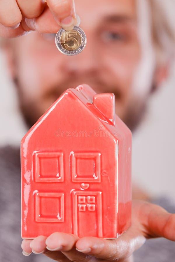 Équipez mettre l'argent dans la tirelire de maison photo stock