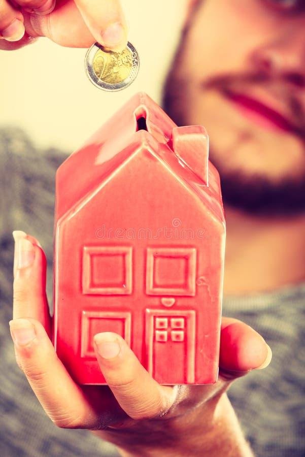Équipez mettre la pièce de monnaie dans la tirelire de maison photo stock