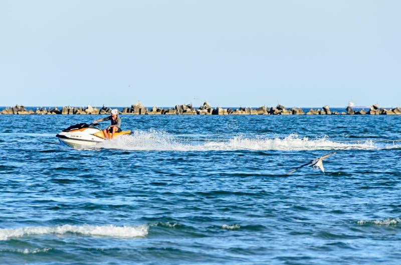 Équipez monter un ski de jet au-dessus de l'eau bleue de la Mer Noire, bateau de banane images stock