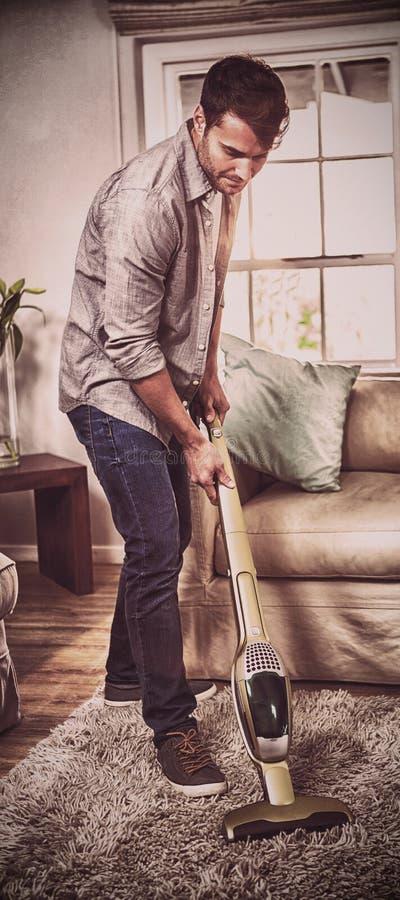Équipez nettoyer un tapis avec un aspirateur photos libres de droits