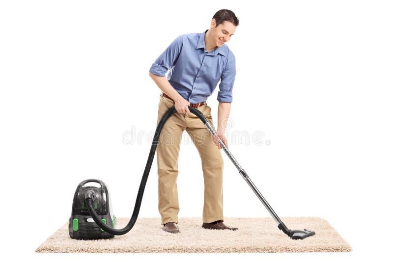 Équipez nettoyer un tapis avec un aspirateur photographie stock libre de droits