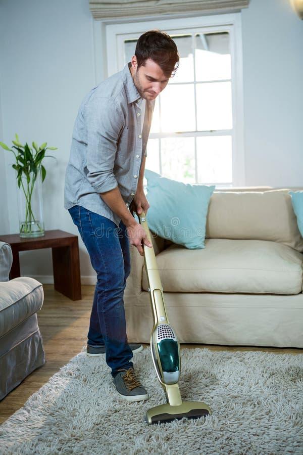 Équipez nettoyer un tapis avec un aspirateur image libre de droits