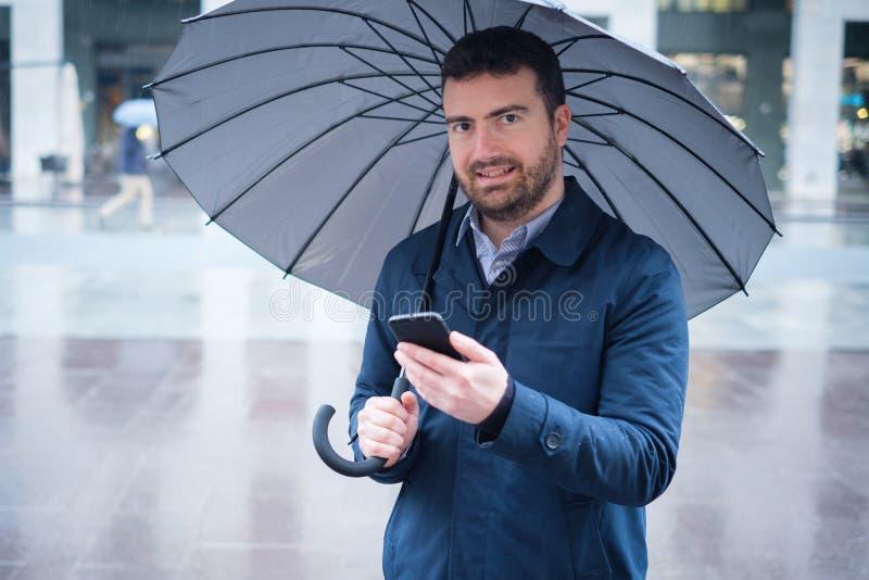 Équipez observer sur le smartphone les prévisions météorologiques un jour pluvieux photographie stock libre de droits