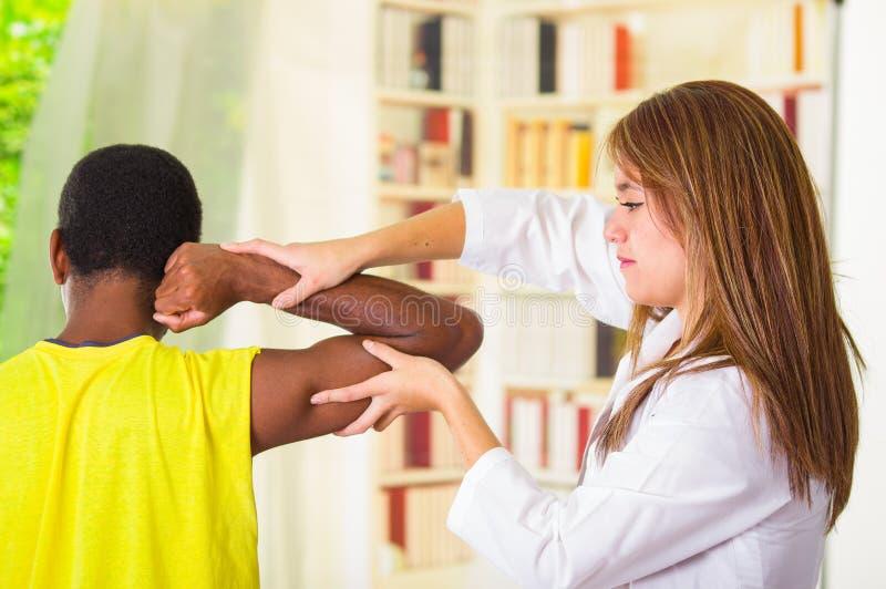 Équipez obtenir le traitement physique de bras du physio- thérapeute, de ses mains travaillant à son épaule et du coude, concept  photographie stock libre de droits