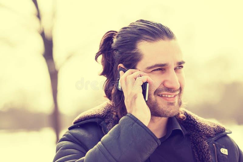 Équipez parler au téléphone intelligent marchant sur la rue image libre de droits