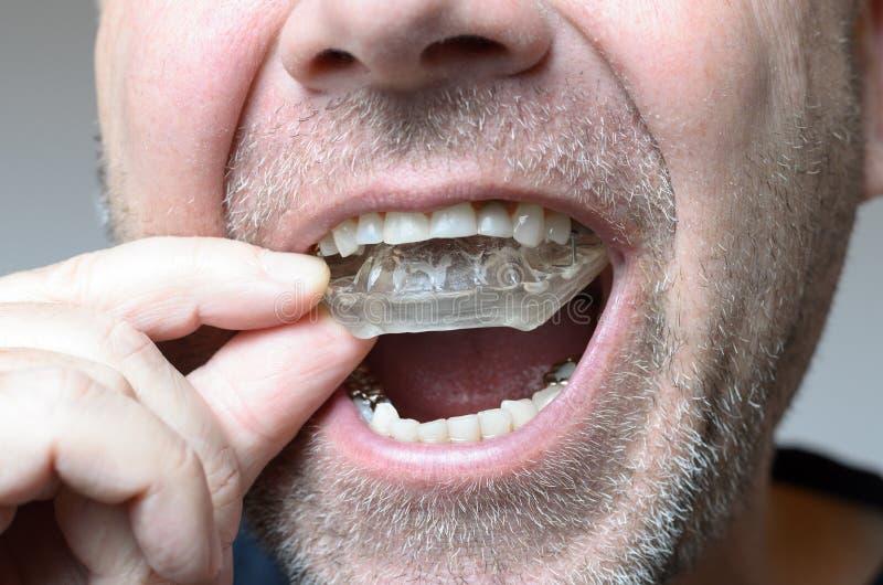 Équipez placer un plat de morsure dans sa bouche photographie stock