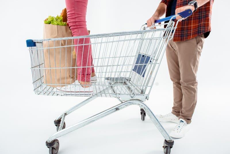 Équipez pousser le caddie avec le jeune sac debout de femme et d'épicerie image libre de droits