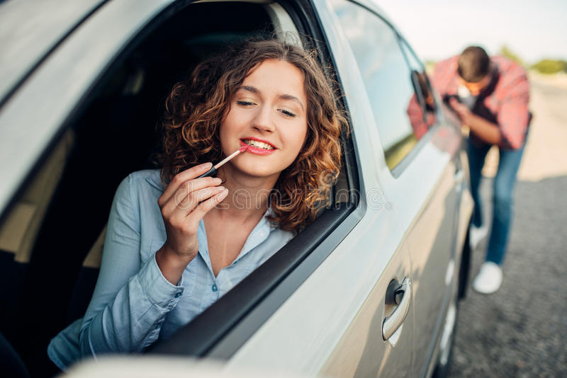 Équipez pousser une voiture cassée, conducteur de femme photographie stock