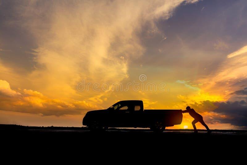 Équipez pousser une voiture cassée en bas de la route photo libre de droits