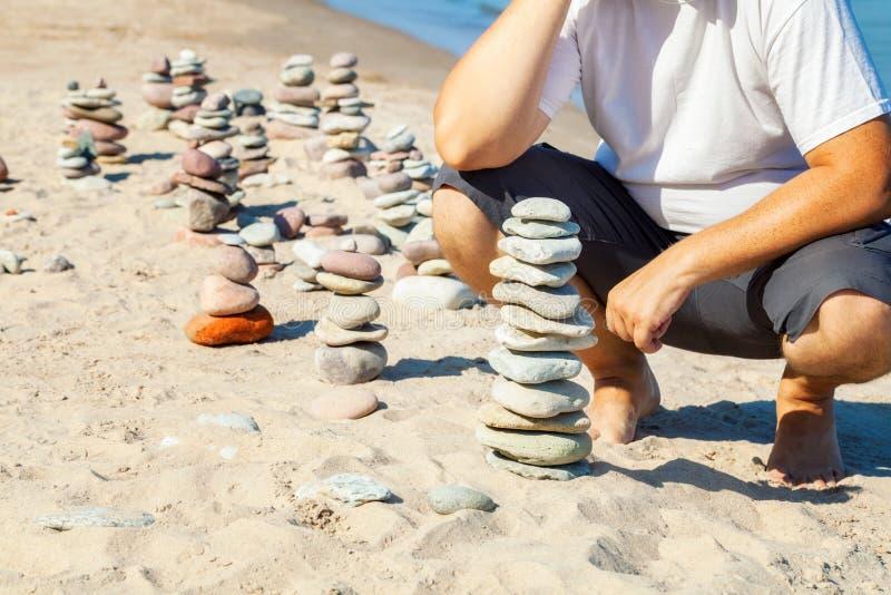 Équipez près des pyramides des pierres équilibrées sur la plage photo libre de droits