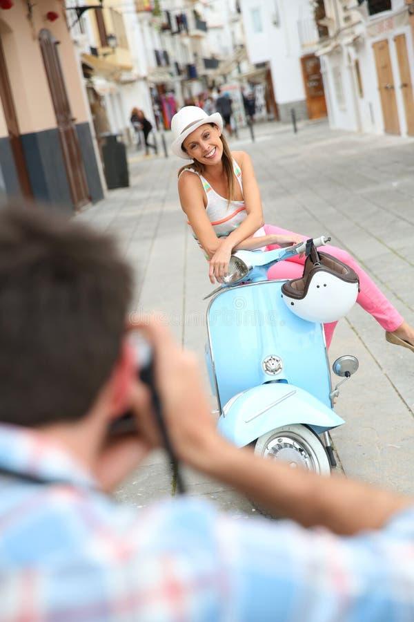 Équipez prendre des photos de son amie sur le scooter images stock