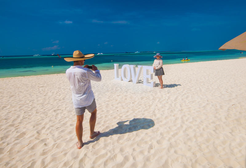 Équipez prendre la photo de sa femme sur la plage sablonneuse, vacances d'été images libres de droits
