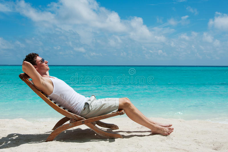 Équipez prendre un bain de soleil sur la plage près de l'océan photo libre de droits