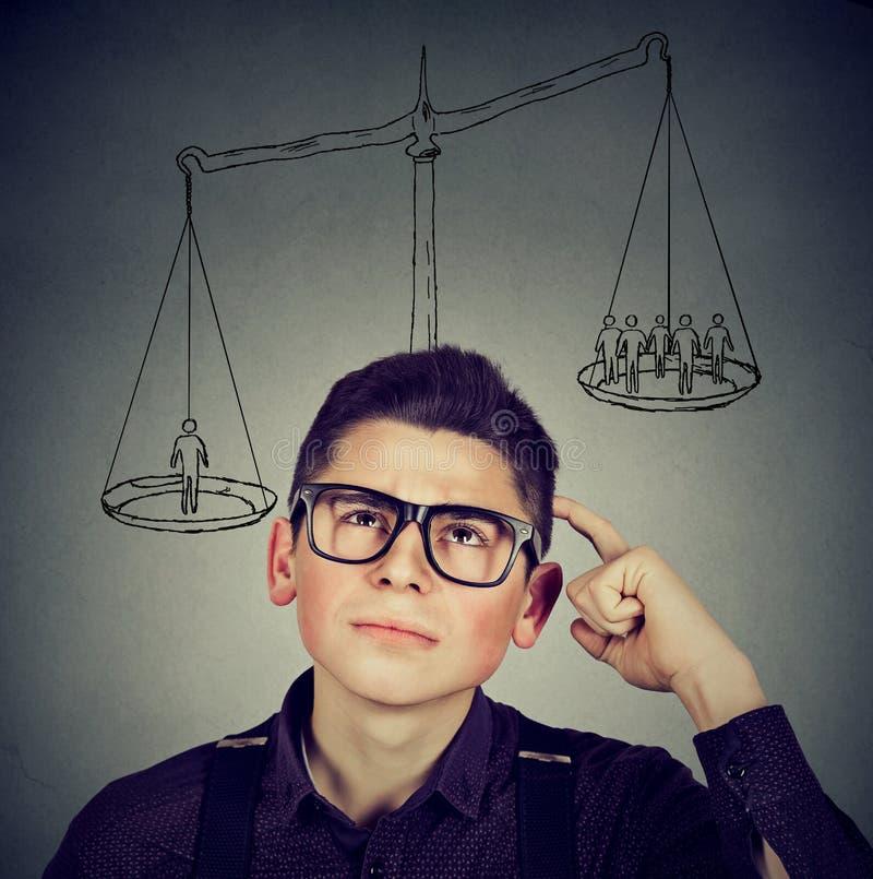 Équipez prendre une décision avec l'échelle au-dessus du chef et des personnes sur un équilibre photo stock