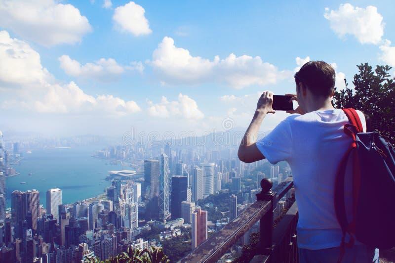 Équipez prennent une photo de téléphone de panorama de bâtiments de Hong Kong photographie stock libre de droits