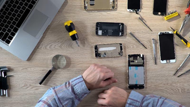 Équipez réparer l'instrument cassé, diagnostiquant des problèmes de téléphone portable, centre de service photographie stock libre de droits